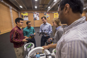 Panos Artemiadis and four other researchers stand together for a photo in the ASU Drone Studio holding devices they test in the facility