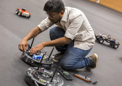 A student makes an adjustment to customizable drone.