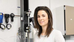 Assistant Professor Julianne Holloway stands in her lab, smiling