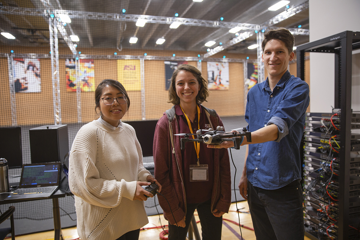 Three students standing holding devices in view of the ASU Drone Studio's servers