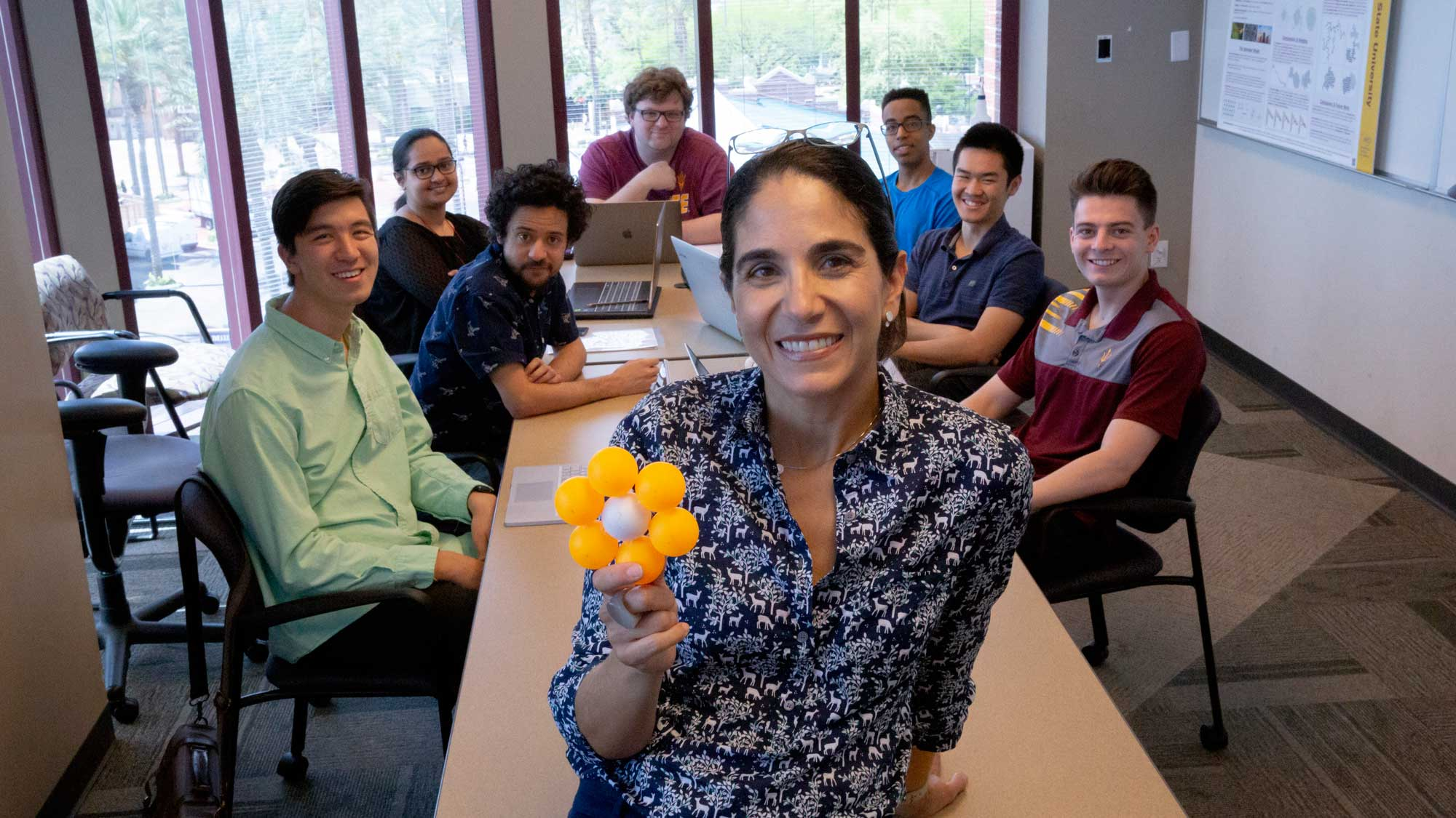 Andrea Richa stands smiling in front of a table full of her researchers in a classroom