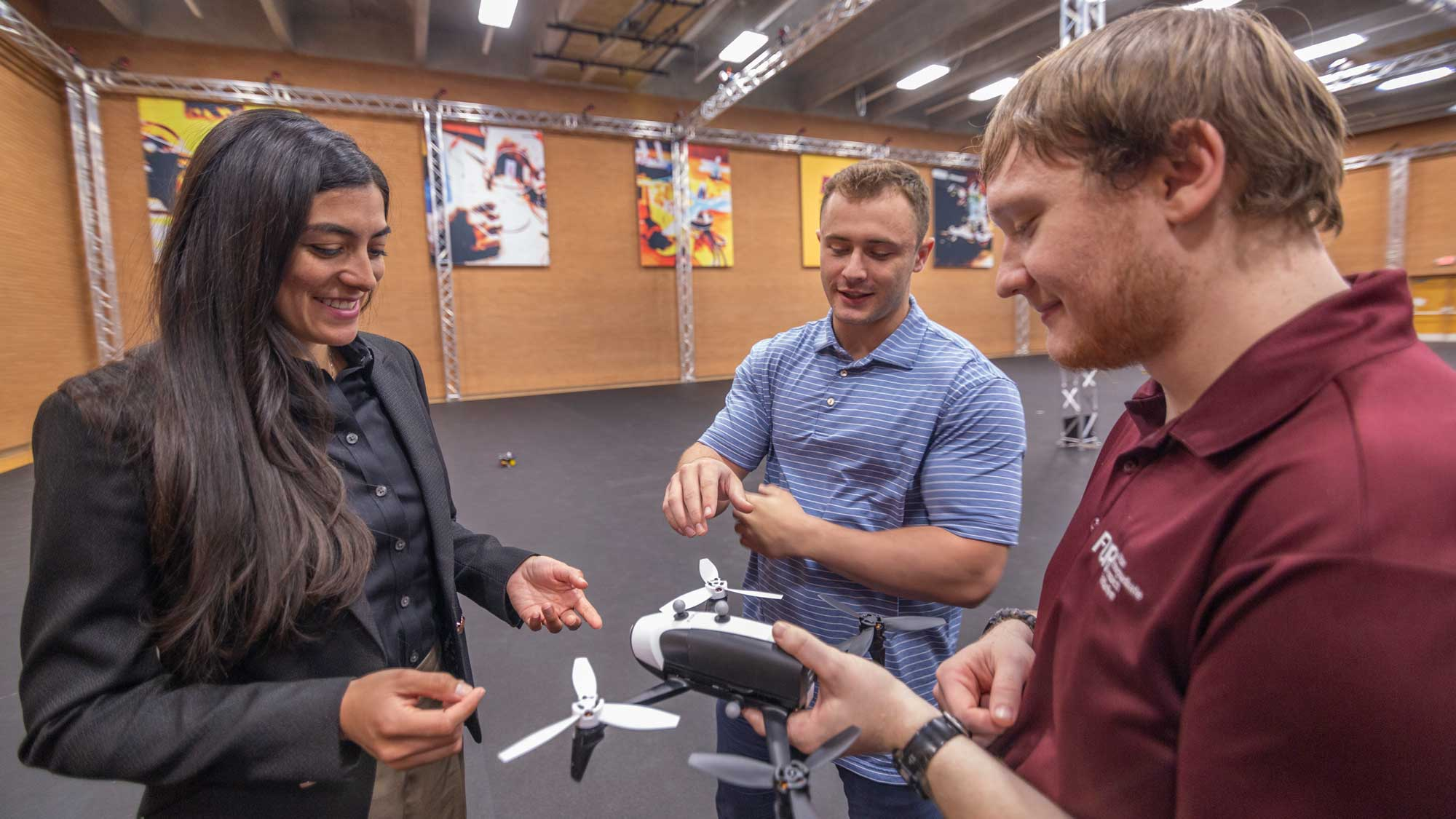Stephanie Gil talks with two researchers in the ASU Drone Studio