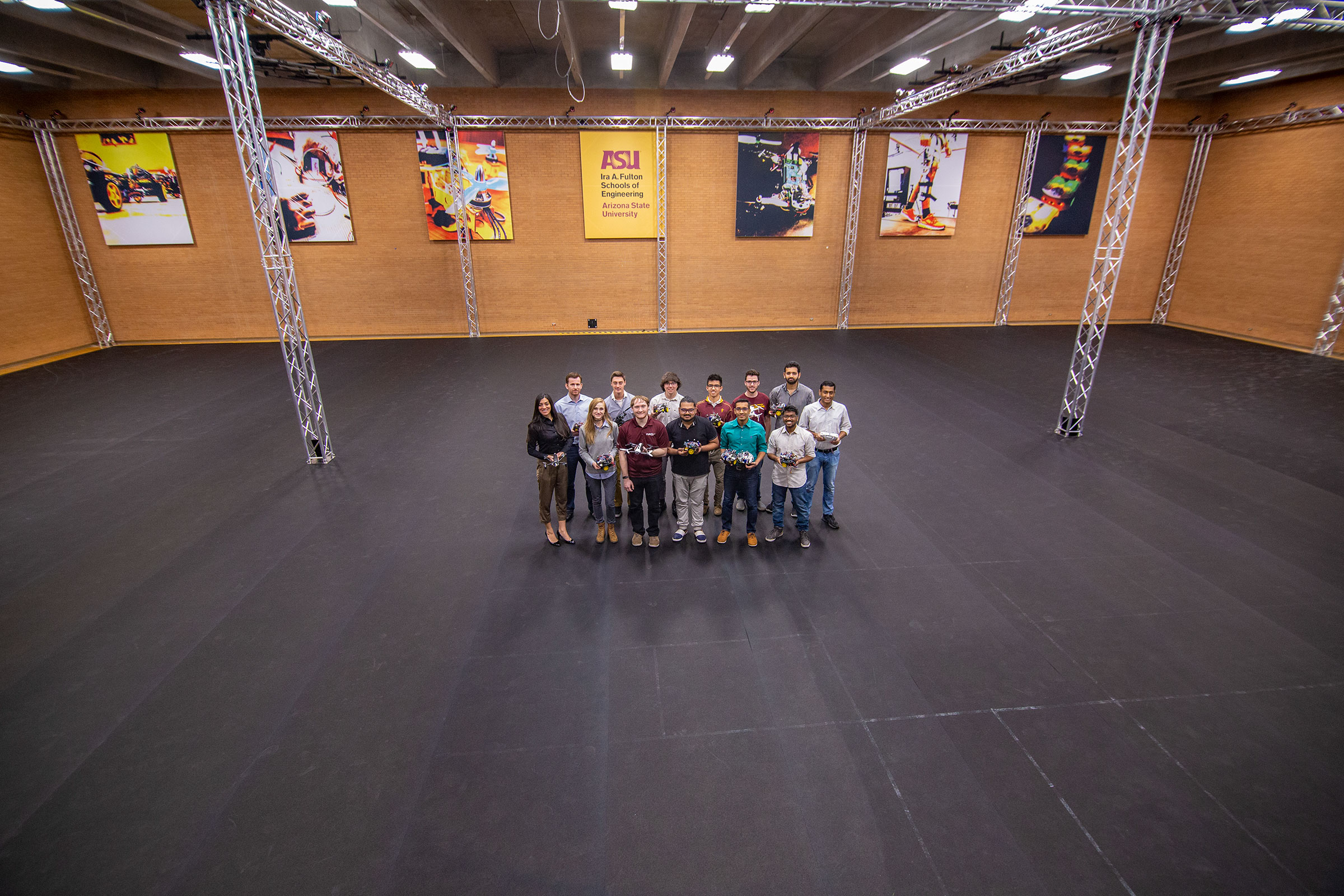 A group of about 20 researchers stand in the middle of the immense ASU Drone Studio, surrounded by tons of open space.