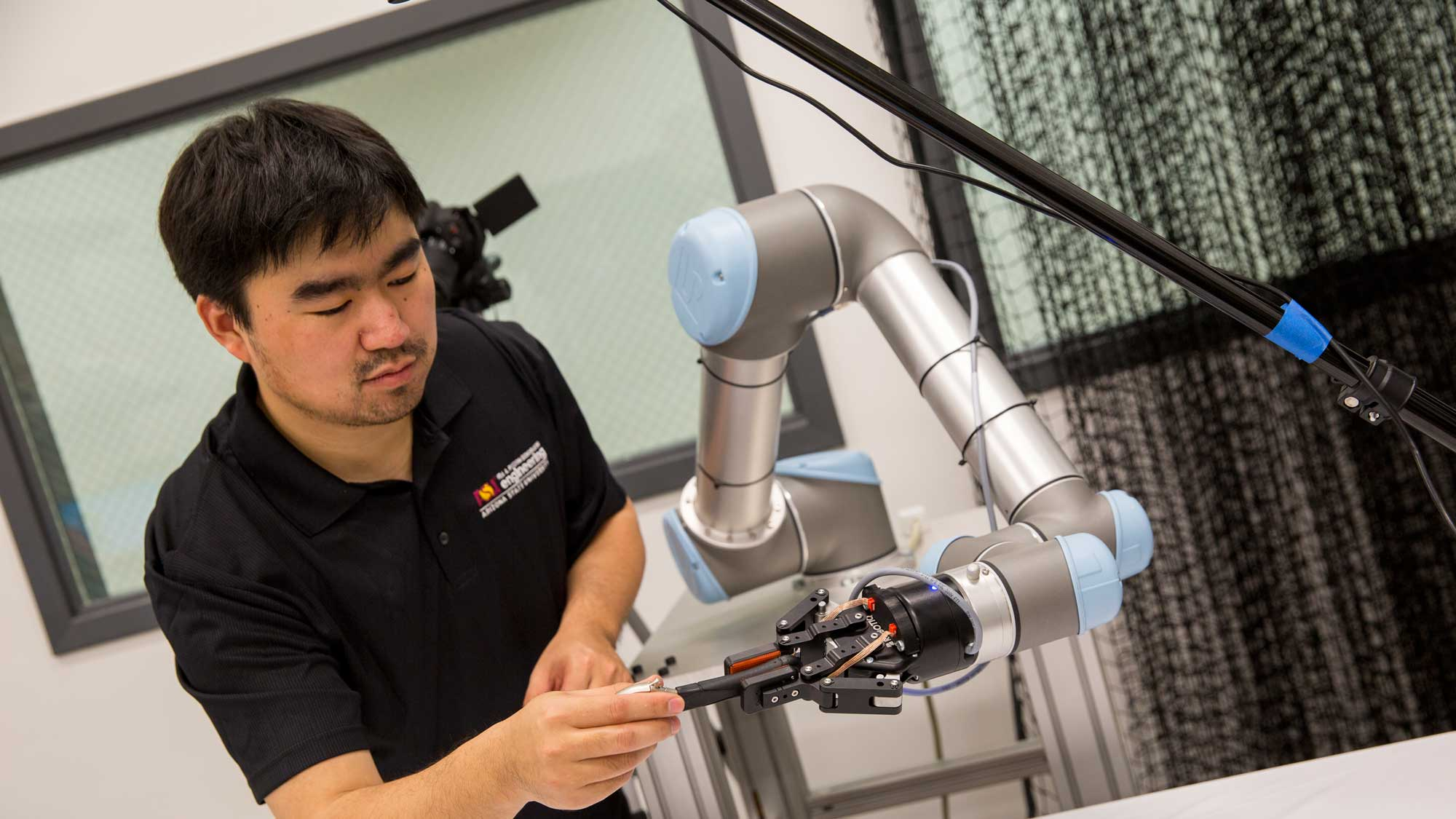a researcher in Wenlong Zhang's lab handles a robotic arm