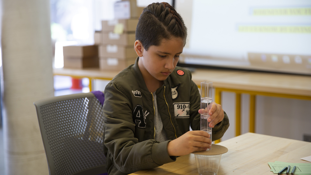 A young girl sits at a table, focused intently on her project, which is a simple water filtration system