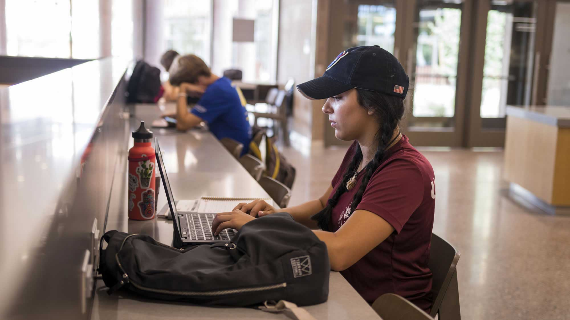 A young woman sits with her laptop, studying at the Tooker House common area