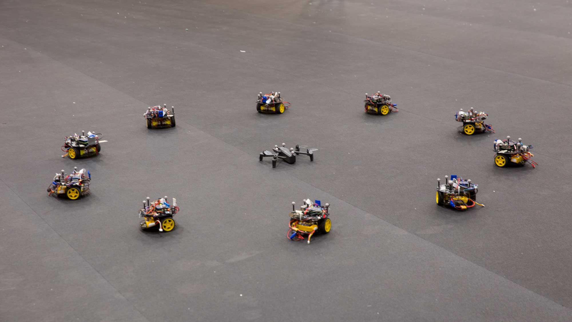 A circle of swarm robots surround a drone on the floor of the ASU Drone studio