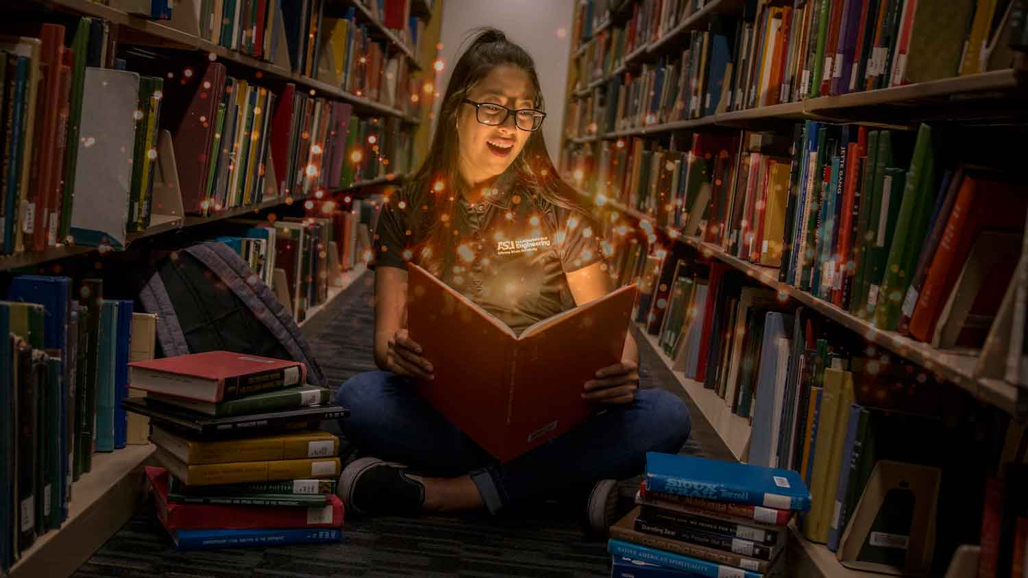A young woman student sits between rows of library shelves reading a book, which appears to have a magical, sparkling effect on her