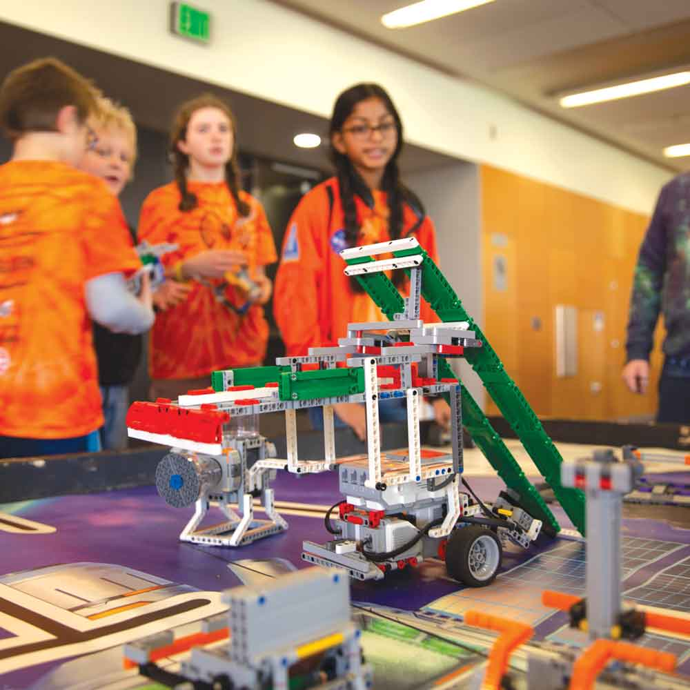 A FIRST LEGO League team stands around their LEGO creation