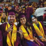 Three graduates show the pitchfork gesture at Convocation