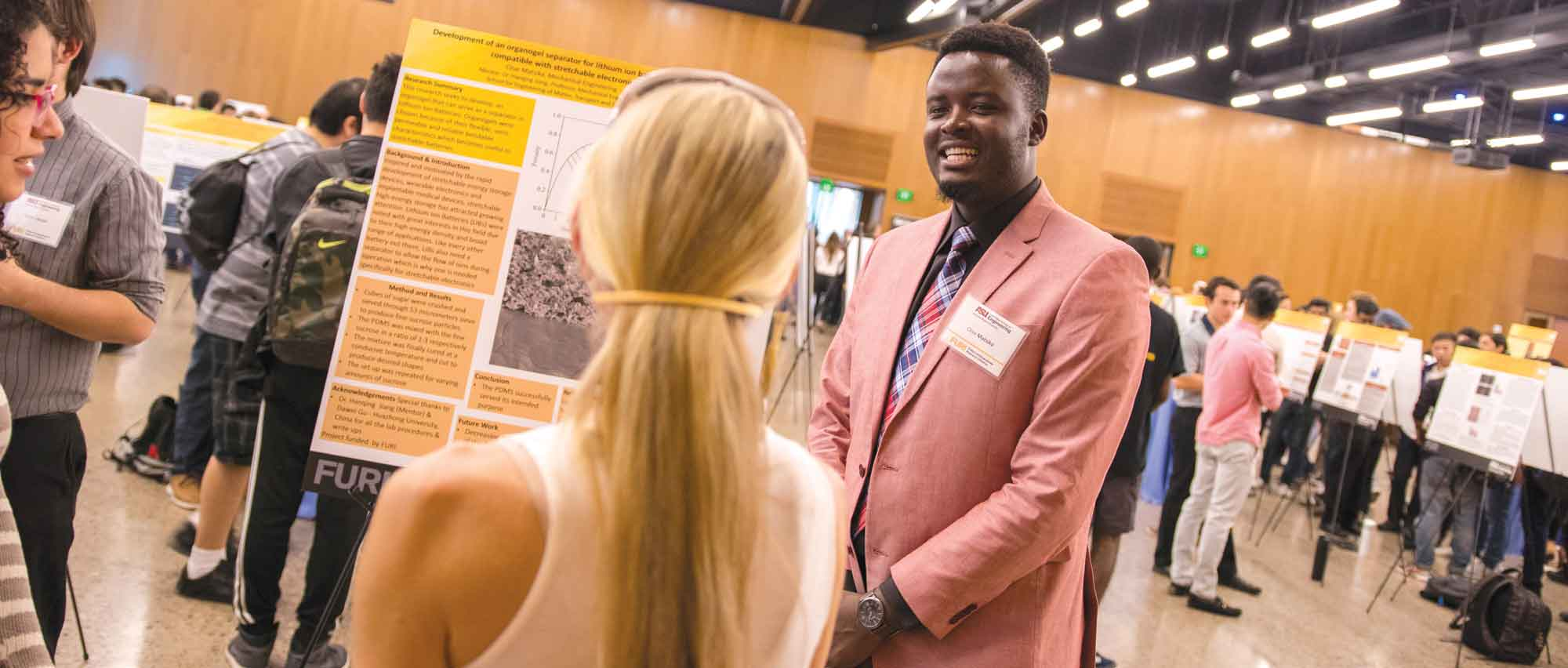 Clive Matsika stands in front of his research poster speaking with an onlooker