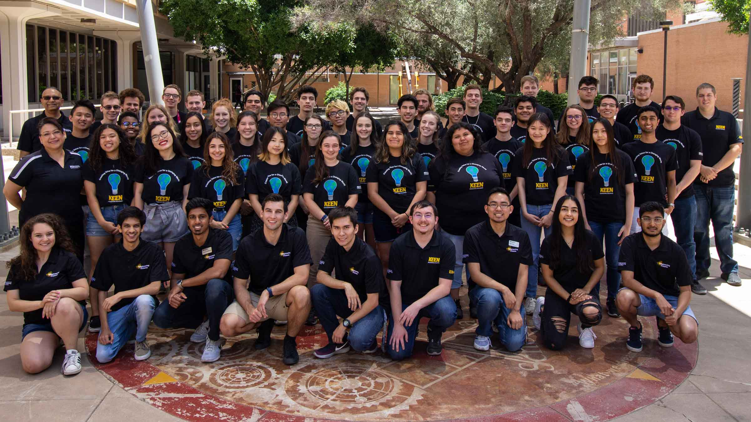A group of about 60 sophomores pose outdoors on ASU's campus for a photo, all wearing their camp t-shirts