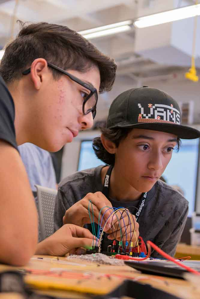 A summer camp counselor helps a summer camp student with a project