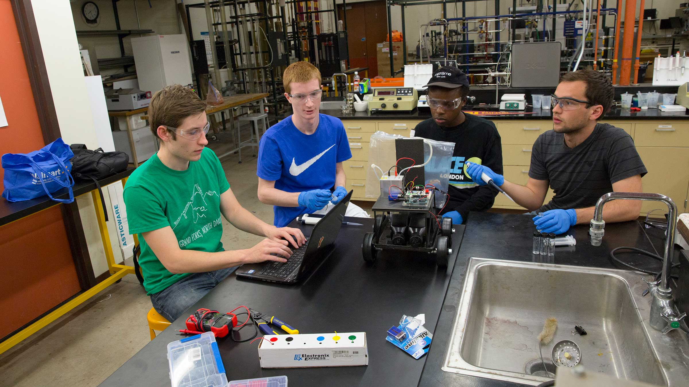 Four male engineering students students work at a lab table on a project