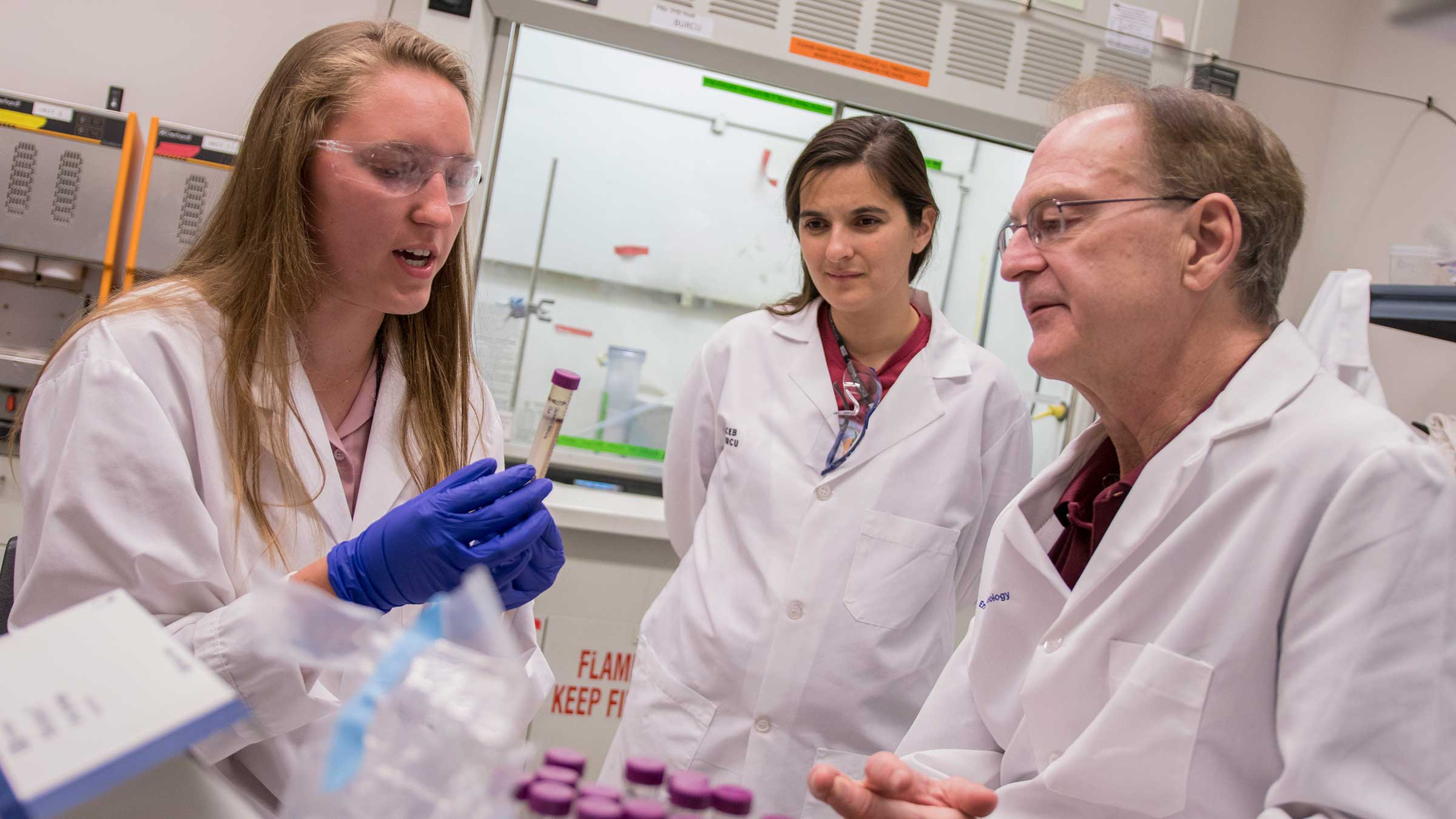Two young women researchers work in a lab with a professor