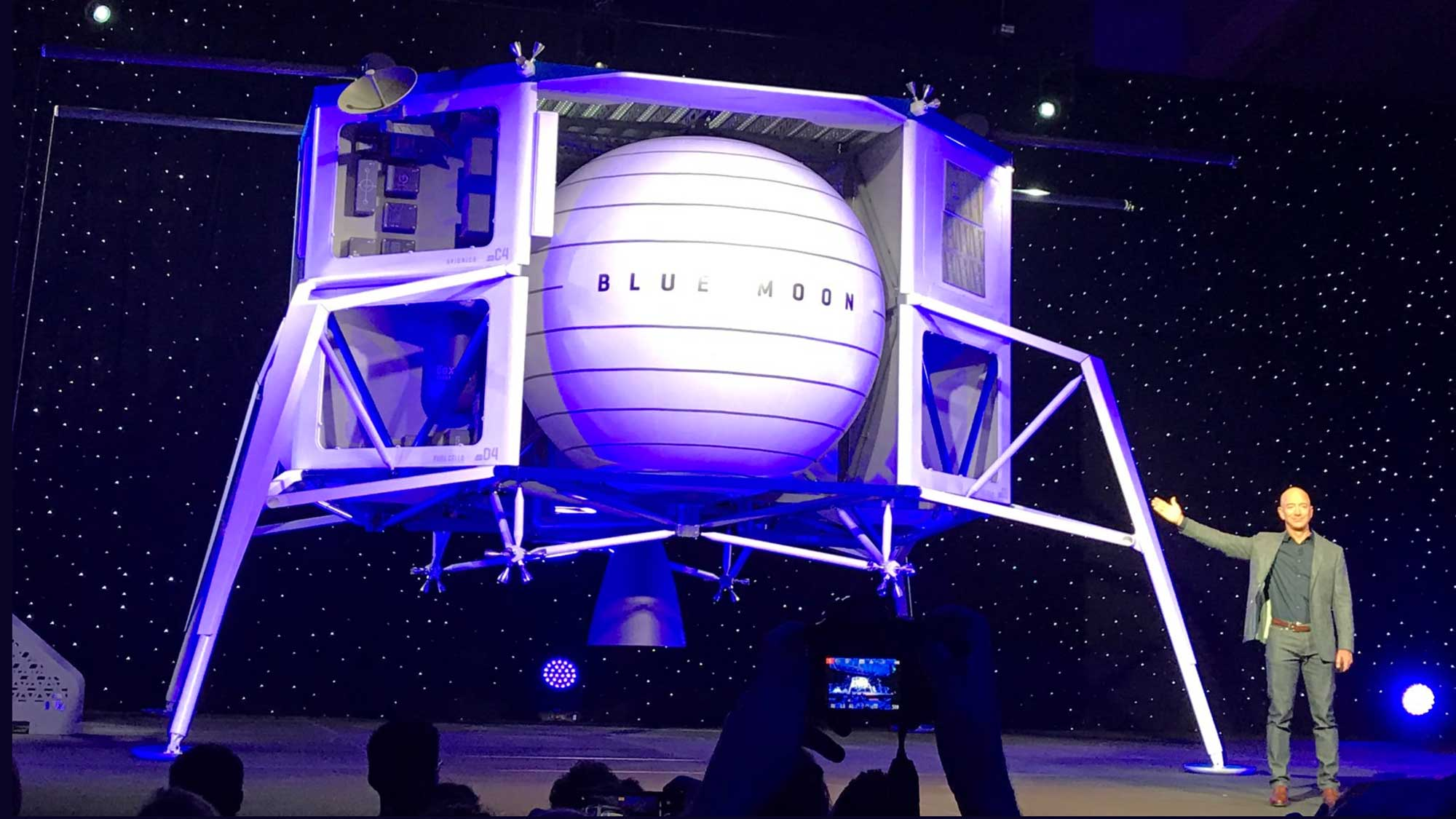 """a man stands on a stage displaying a """"Blue Moon"""" Blue Origin spacecraft"""