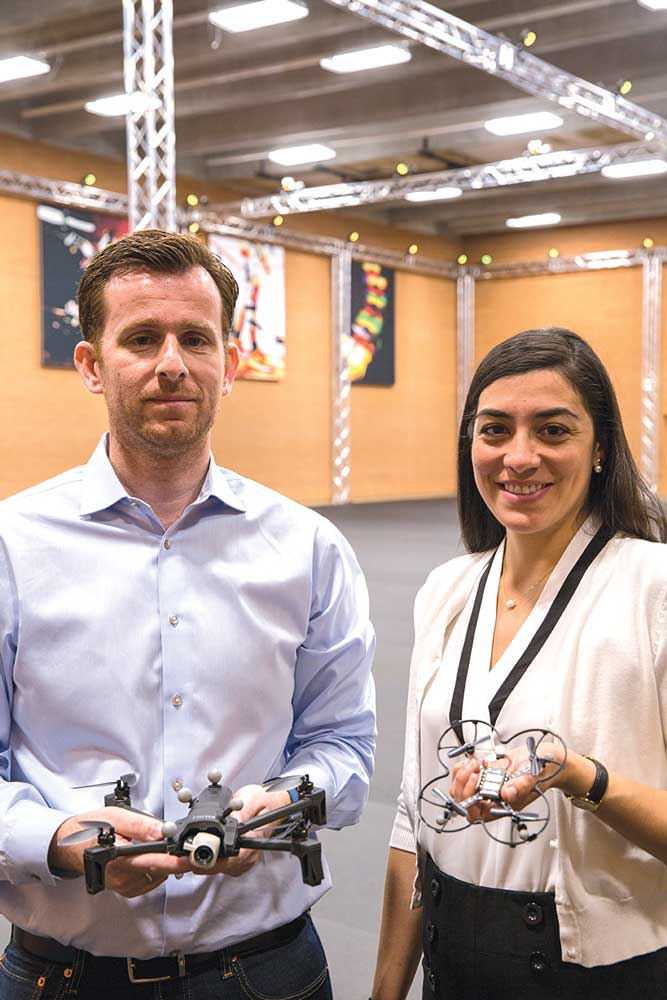 Panos Artemiadis and Stephanie Gil stand together for a photo in the ASU Drone Studio, holding devices they test in the facility