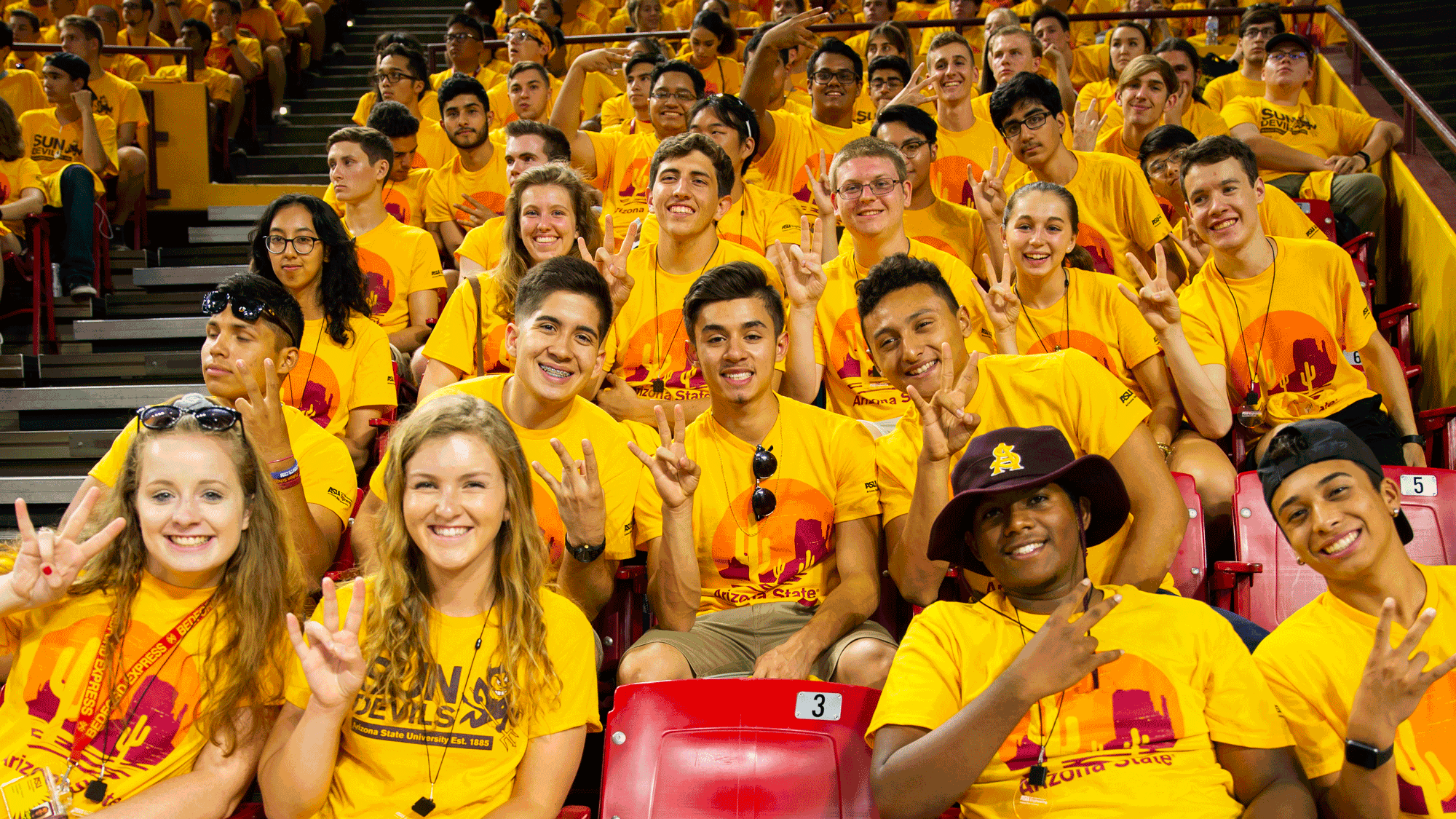 A large group of students sit in the stands of Wells Fargo arena at the Fall Welcome, smiling for the camera and making the ASU pitchfork gesture