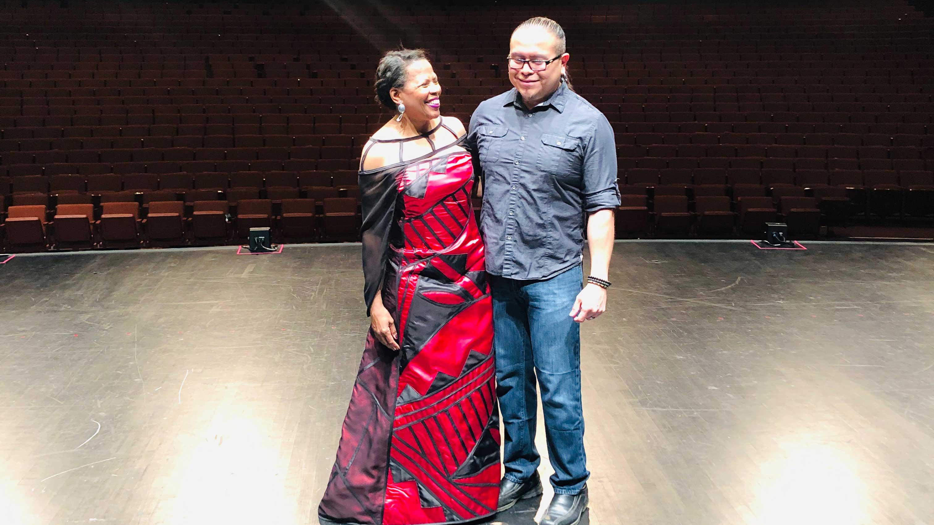 Colleen Jennings-Roggensack and Loren Aragon are on stage at Gammage Auditorium, whre Jennings-Roggensack is wearing the dress Aragon designed