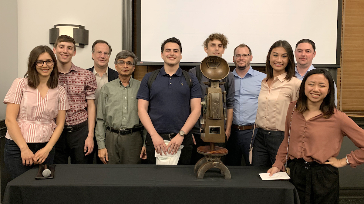 A group of 10 people including Materials Bowl teams and mentors stand around the Materials Bowl trophy they won.