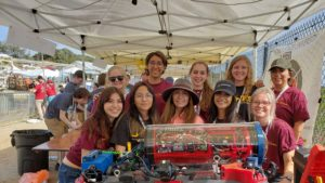 The all-women Desert WAVE underwater robotics team poses for a team photo with their robot
