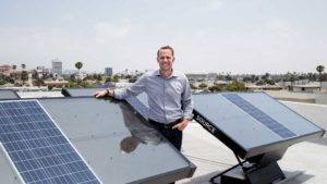 Cody Friesen stands on a roof among several SOURCE hydropanels, which extract clean water from the air using only solar power. Friesen invented the panels and won the 2019 Lemelson-MIT Prize for this and other inventions for the developing world.
