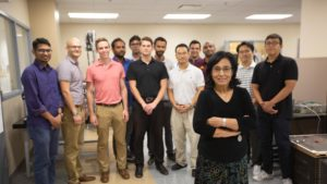Regents Professor Aditi Chattopadhyay stands, arms crossed, in front of her large lab team