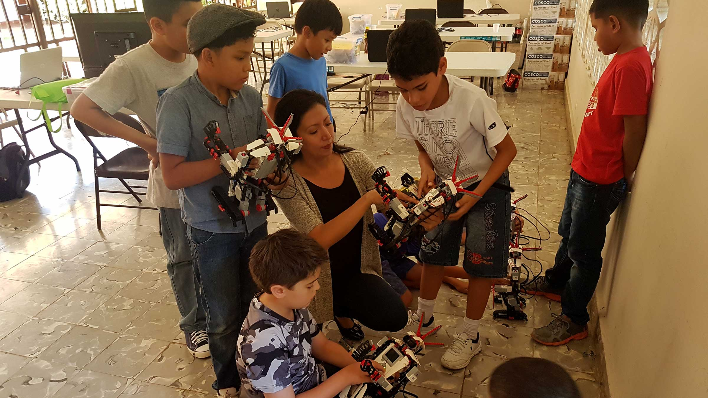 Victoria Serrano is shown working with a group of Panamanian students using LEGO MINDSTORMS robotic kits.