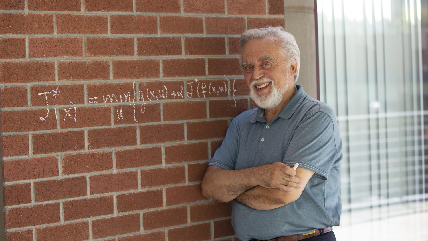Dimitri Bertsekas stands in front of an ASU building on which he's written a mathematical equation in chalk