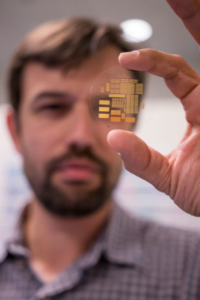 George Trichopoulos holds a small array of antennas in a wafer.