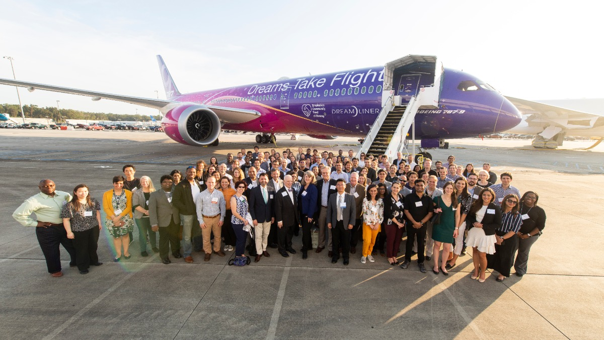 Around 100 Symposium attendees stand together for a group shot in front of a Boeing 787 Dreamliner