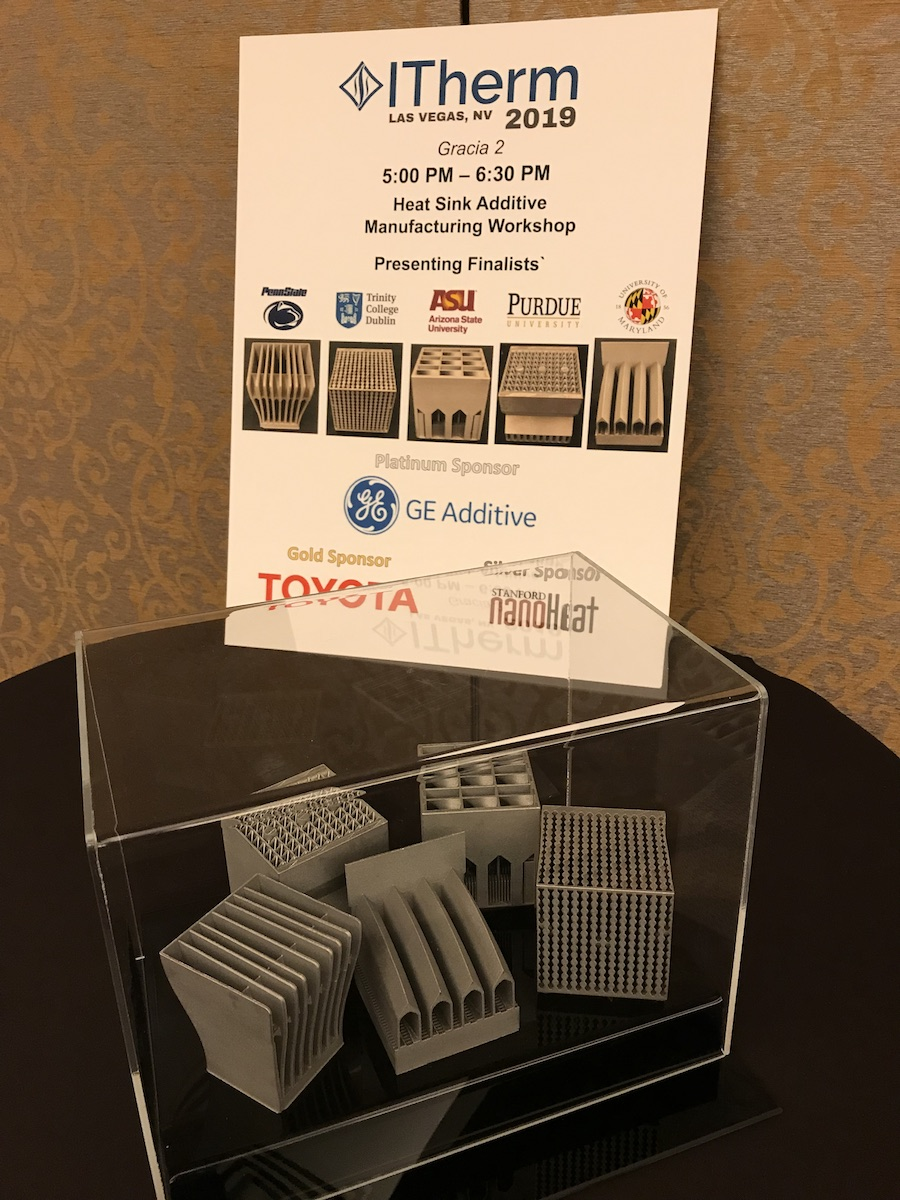 Table with iTherm 3D-printed heat sink competition poster and the five 3D-printed heat sink finalists structures in a plexiglass case