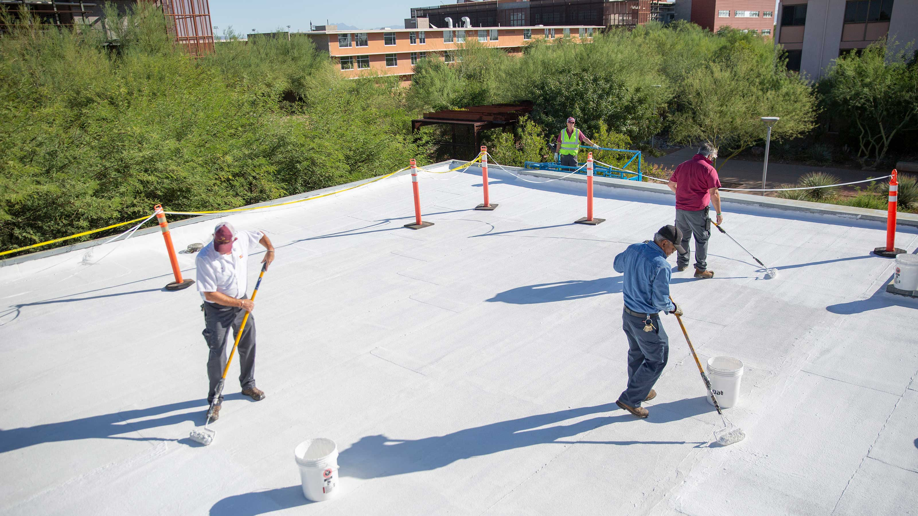 Workers on a flat building roof are rolling a bright white material onto the roof
