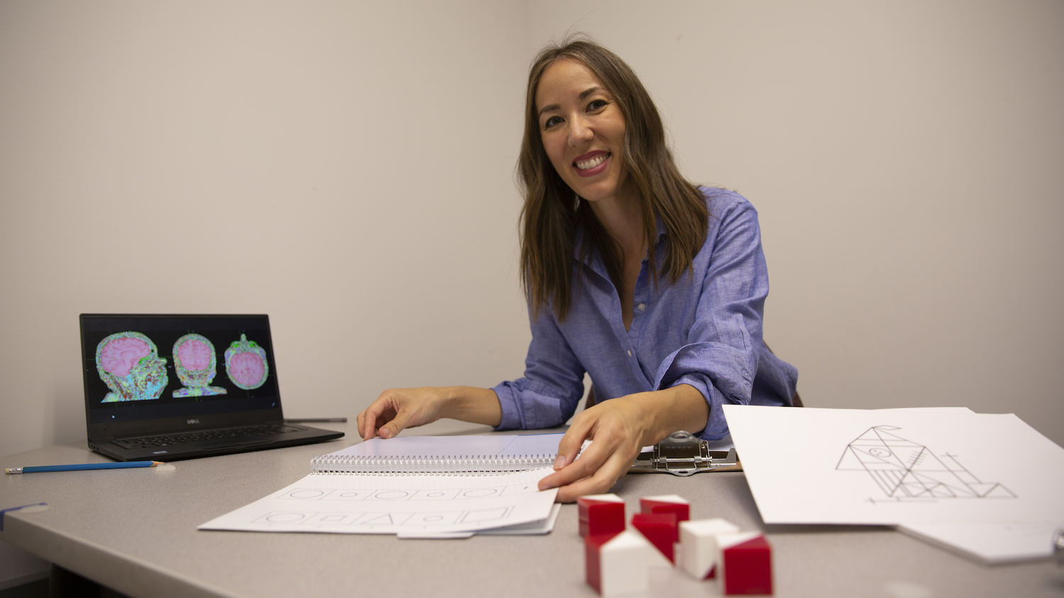 Sydney Schaefer sits at her desk displaying some of the low-cost cognitive tests (papers with drawings) she uses in her research