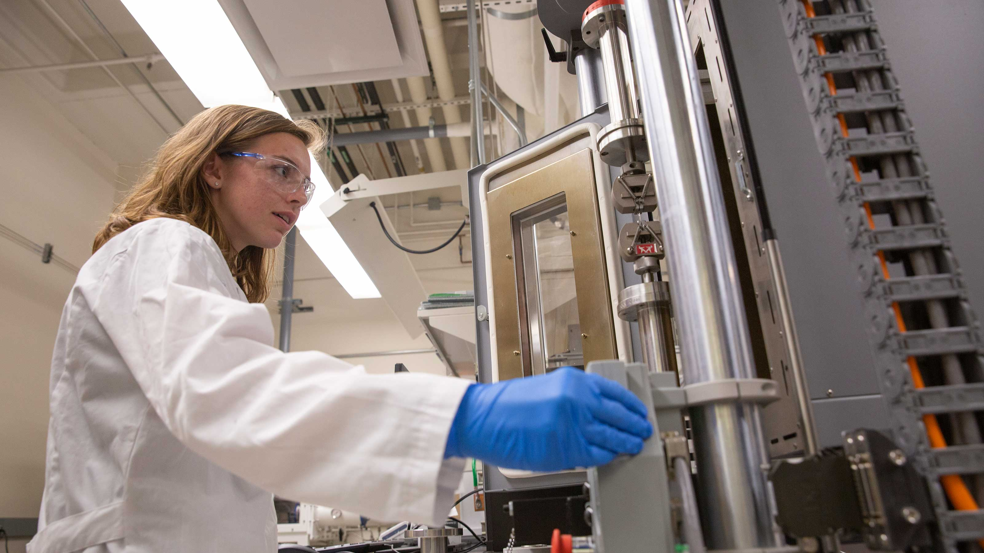 Alexis Hocken works in a lab performing mechanical testing with an Instron instrument used to investigate how much load the sample being tested can handle before breakage.