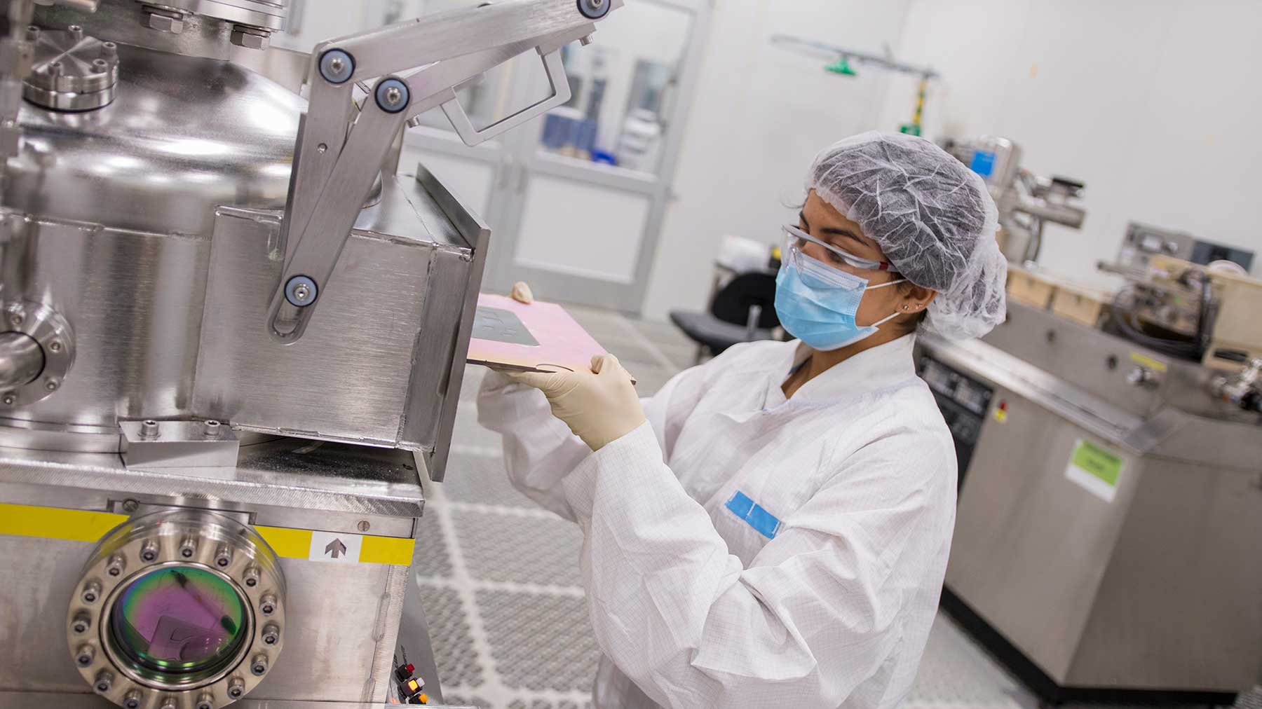 a solar researcher in full white lab gear places an object into a piece of lab equipment
