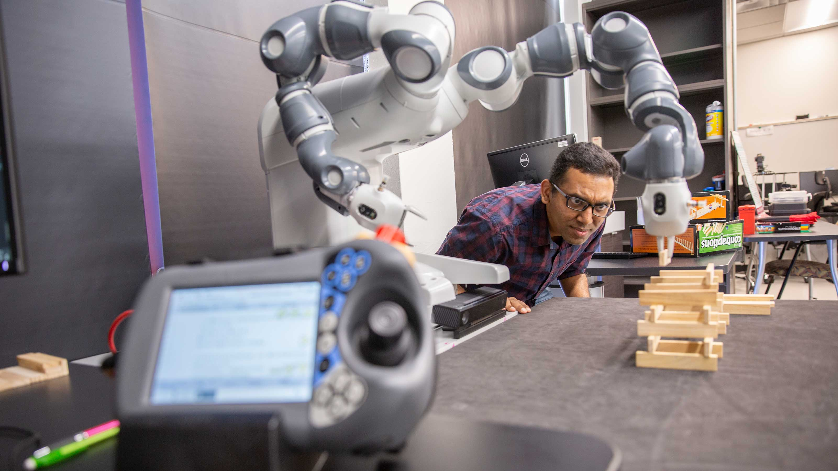 A member of Siddharth Srivastava's lab looks on as an autonomous robot builds a wood block tower