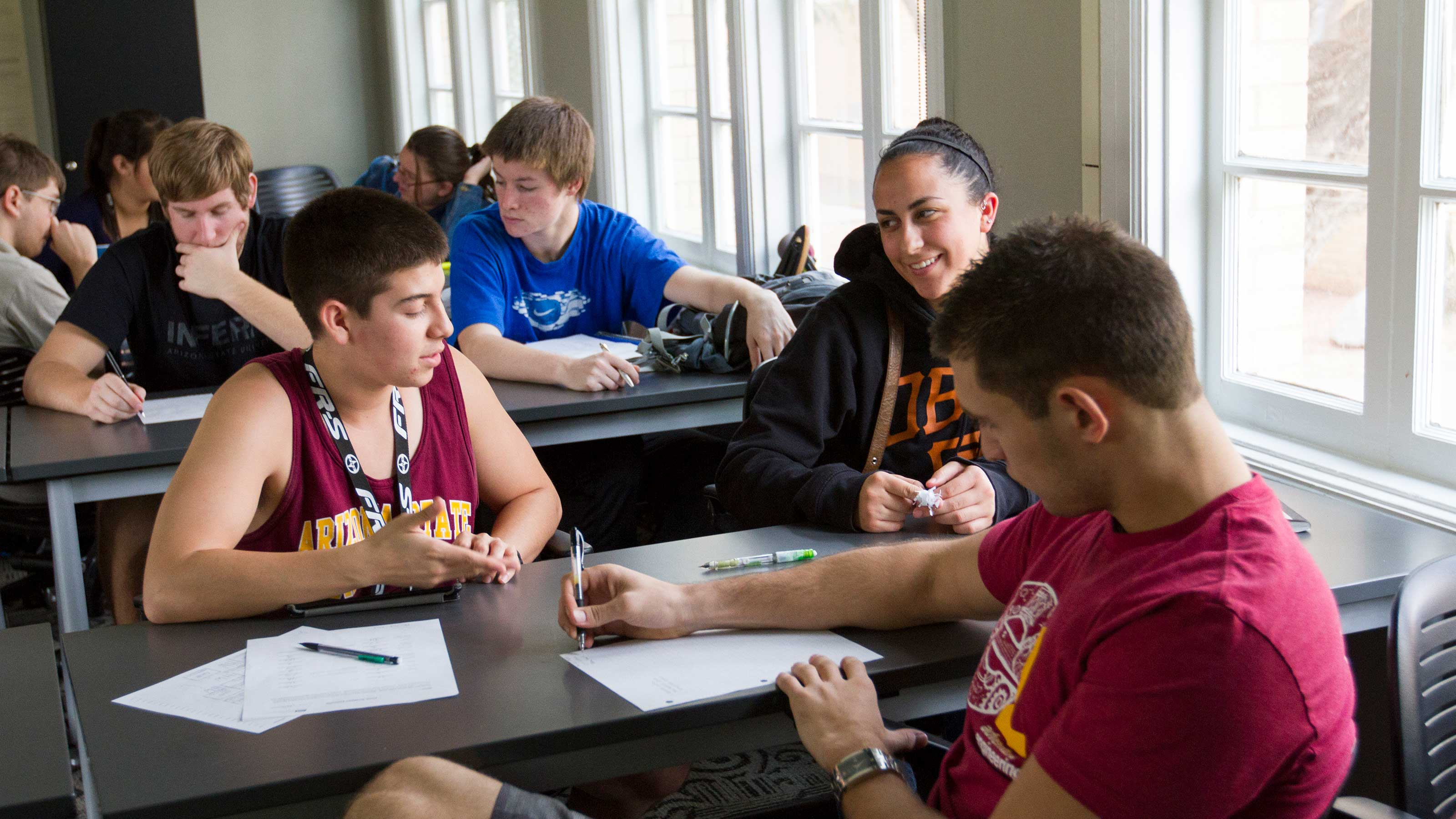 A couple of students work at a table together with an undergraduate teaching assistant