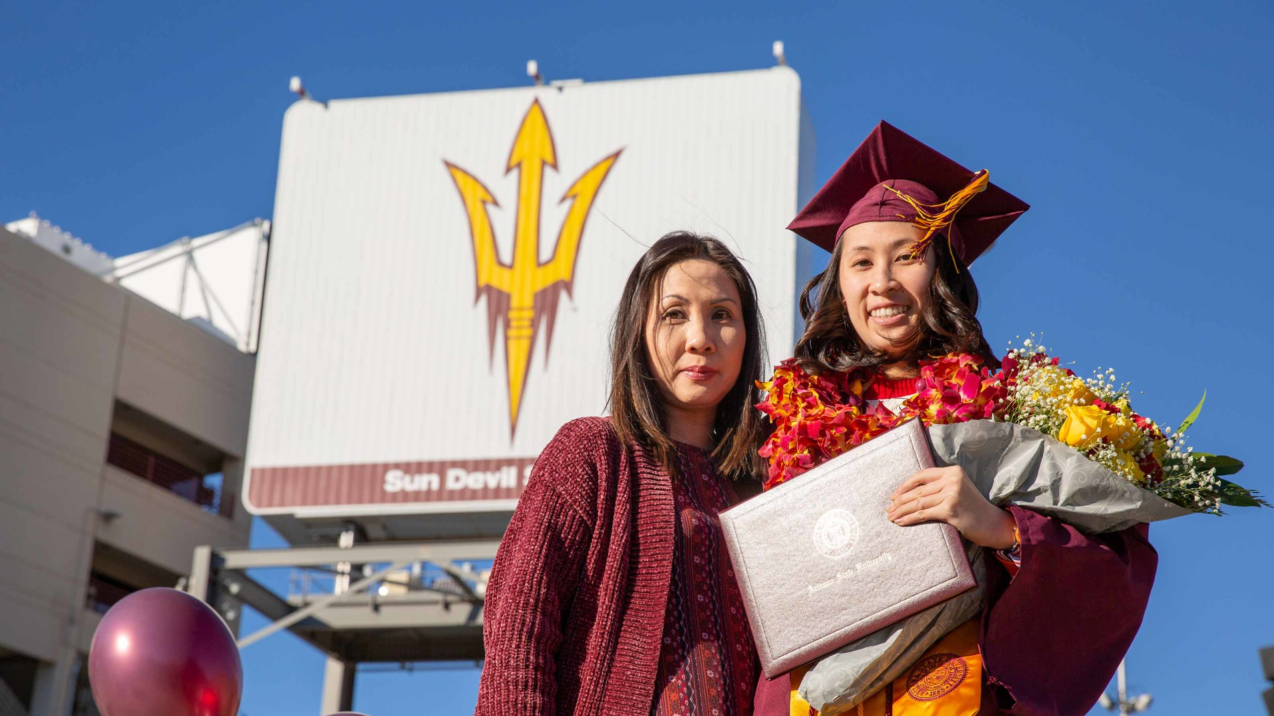 A graduate and her mother pose together for a Convocation photo, the woman in regalia, grinning, and the mother, emotional, slightly smiling