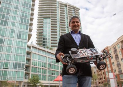 Aviral Shrivastava stands outside in downtown Tempe Arizona holding his small autonomous vehicle