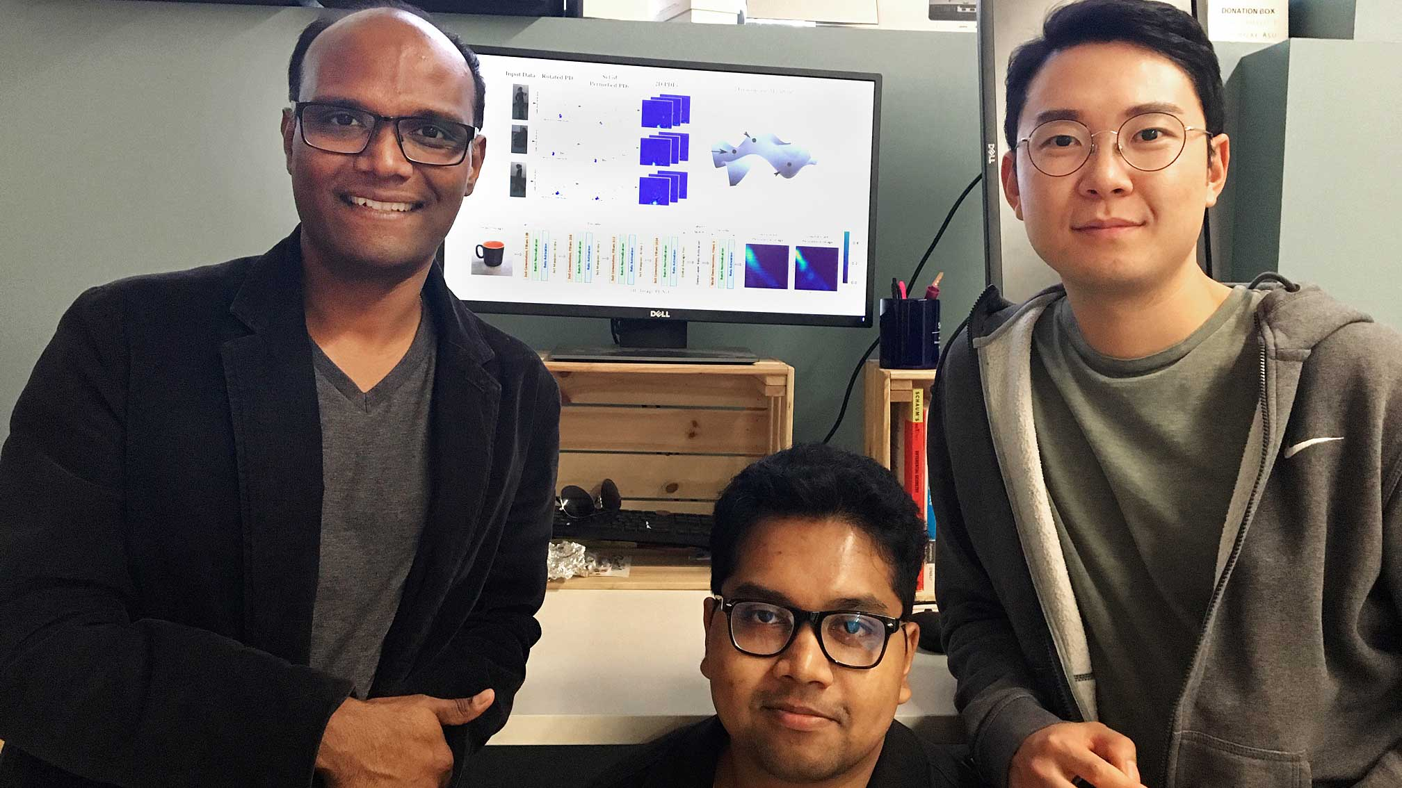 Pavan Turaga and his research team of two students pose in the lab in front of a computer screen of data