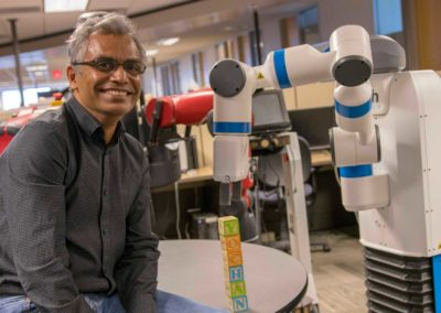 Rao Kambhampati poses for the camera in his lab next to a robot that has just stacked some alphabet blocks