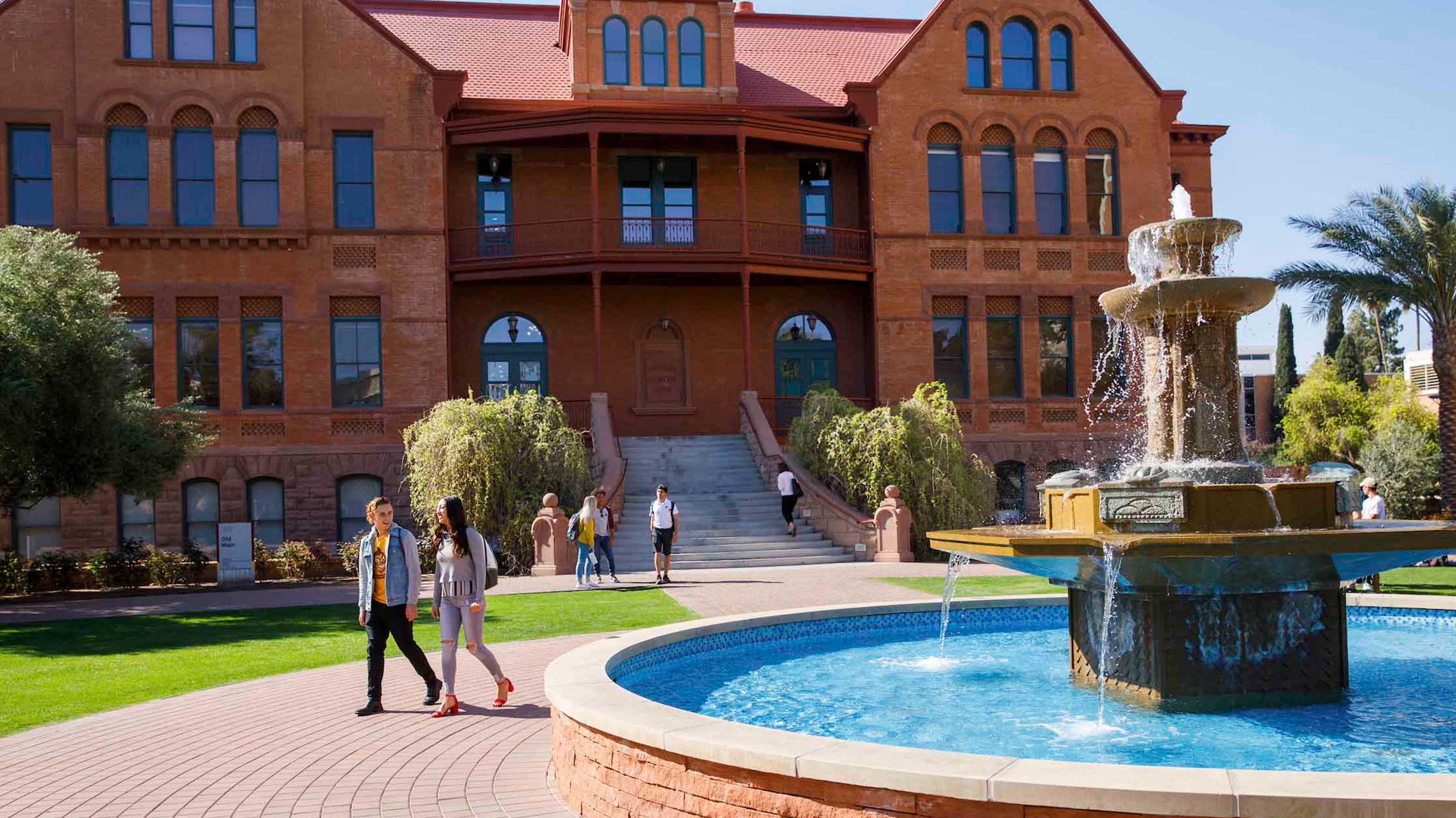 View of students walking in front of ASU's iconic first building, Old Main