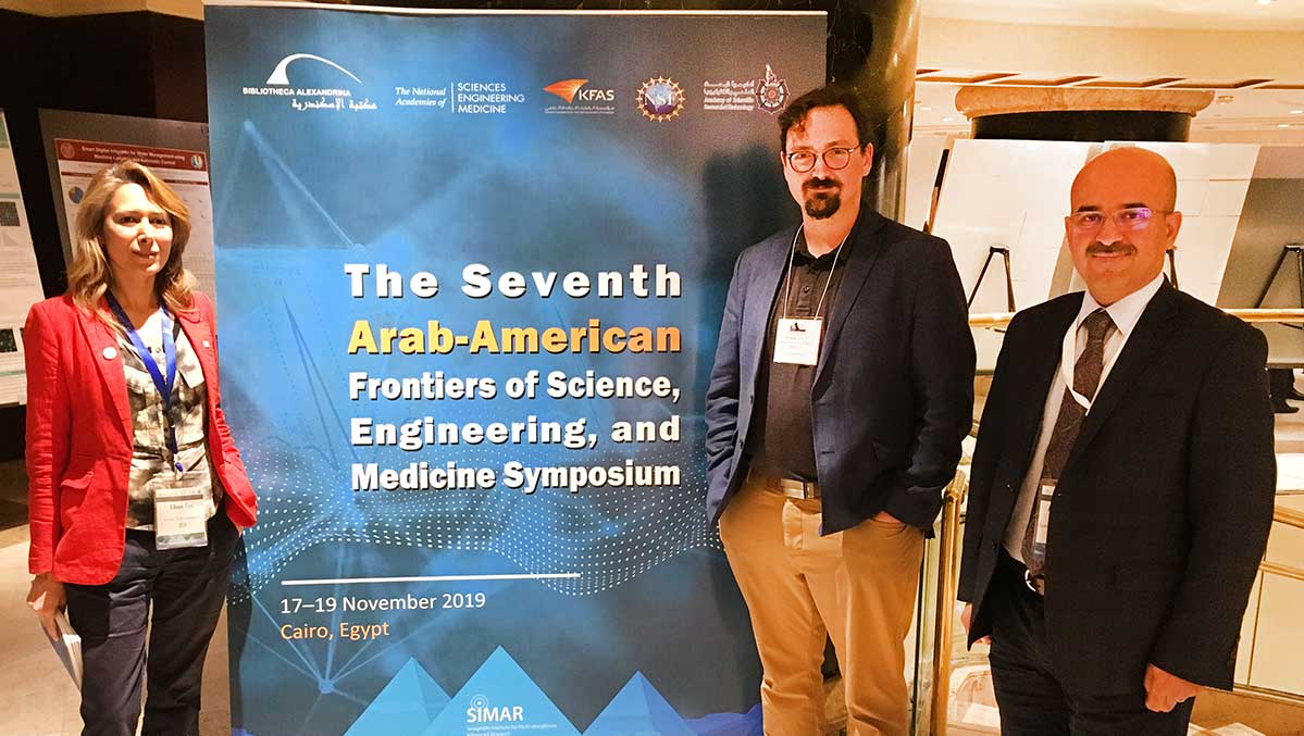 Elham Fini and Francois Perreault stand together in front of a poster for the 7th Arab-American Frontiers of Science symposium