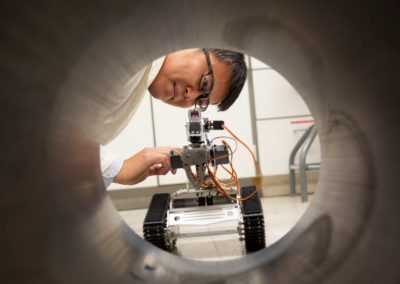 Yongming Liu looks closely at a robot on rotating, tank-like tread that he is preparing to send down a pipeline