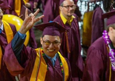 A SHPE graduate poses for the camera as he exits the Fulton Schools convocation
