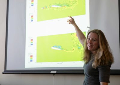 Yulia Peet stands pointing to a graph of data on a screen