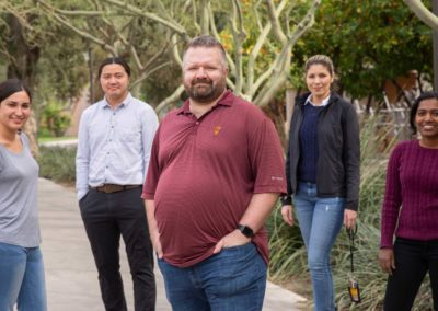 Christian Hoover stands on campus with members of his lab