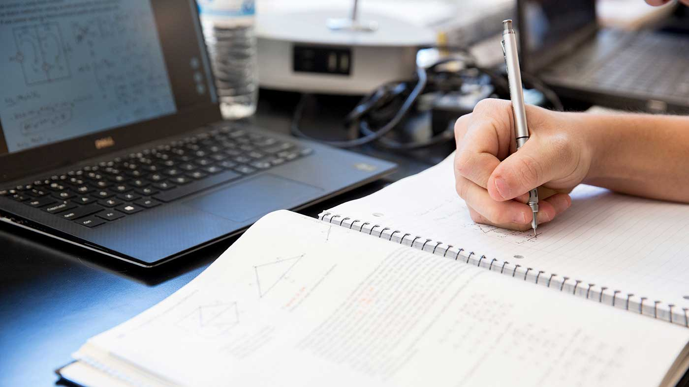 close up of student working at a laptop alone and writing with a pen