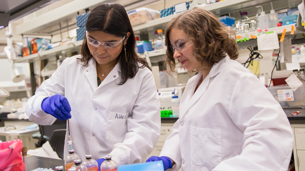 Two women work in a lab together
